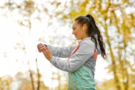 Foto de Woman looking at fitness tracker in autumn park - Imagen libre de derechos