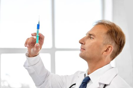 Foto de Smiling doctor with syringe at hospital - Imagen libre de derechos