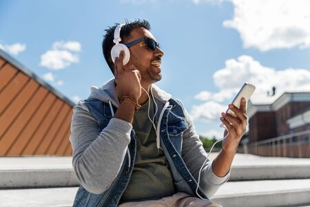 Photo pour Man with smartphone and headphones on roof top - image libre de droit
