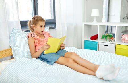 Photo pour happy little girl reading book at home - image libre de droit