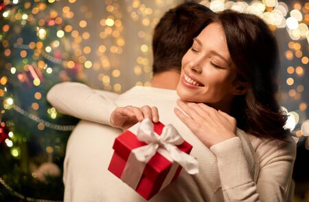 Foto de happy couple with christmas gift hugging at home - Imagen libre de derechos