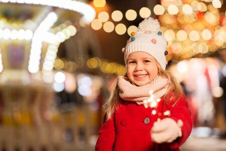 Photo pour happy girl with sparkler at christmas market - image libre de droit