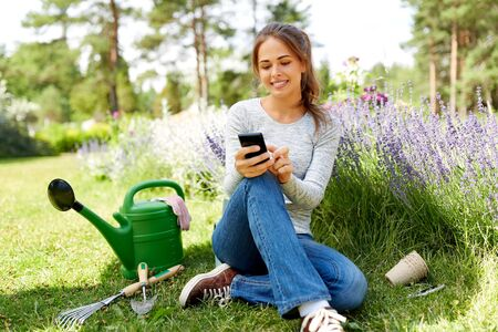 Photo pour woman with smartphone and garden tools in summer - image libre de droit