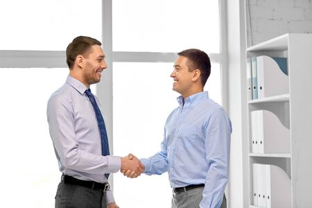Photo for Happy businessmen making handshake at office - Royalty Free Image