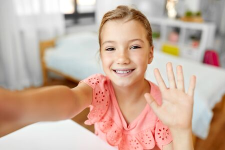 Photo pour happy girl taking selfie and waving hand at home - image libre de droit