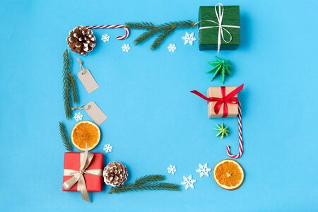 Photo pour winter holidays, new year and christmas concept - frame made of gift boxes, fir tree branches, tags and decorations on blue background - image libre de droit