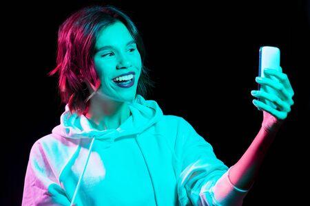 Photo pour Woman taking selfie by smartphone in neon lights - image libre de droit