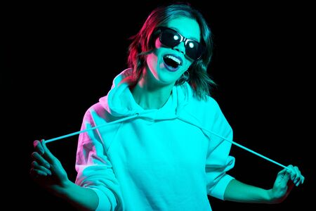 Photo pour woman wearing hoodie in neon lights over black - image libre de droit