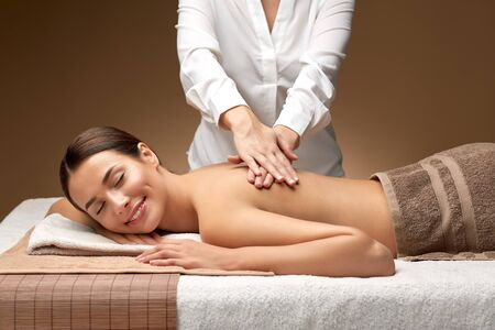 Foto de woman lying and having back massage at spa - Imagen libre de derechos