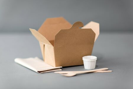 Photo pour package, recycling and eating concept - disposable box for takeaway food with wooden fork, knife and napkin on table - image libre de droit