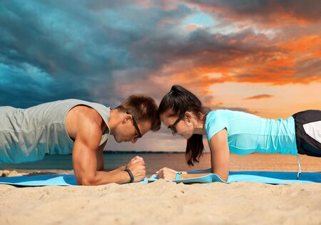 Foto de fitness, sport and lifestyle concept - couple doing plank exercise on summer beach over sea and sunset sky on background - Imagen libre de derechos