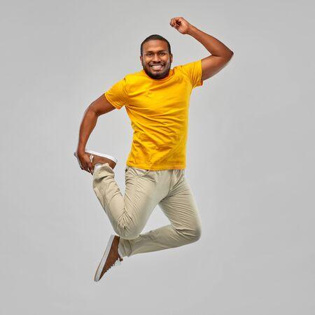 Foto de smiling young african american man jumping in air - Imagen libre de derechos