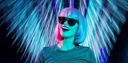 Photo pour happy woman in pink wig and black sunglasses - image libre de droit