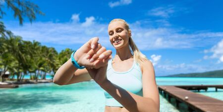 Foto de happy woman with fitness tracker and earphones - Imagen libre de derechos