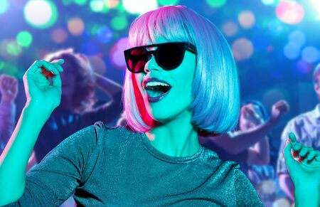 Photo for nightlife, entertainment and people concept - happy young woman wearing pink wig and black sunglasses dancing at nightclub over lights background - Royalty Free Image