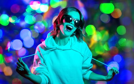 Photo pour nightlife, fashion and people concept - happy young woman in black sunglasses wearing hoodie over night lights background - image libre de droit