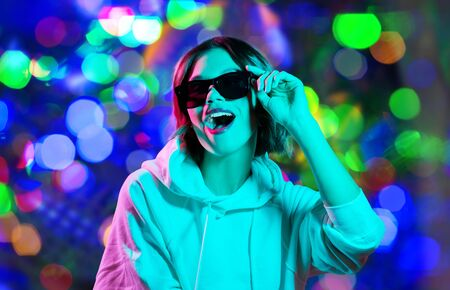 Photo pour woman in hoodie with sunglasses over night lights - image libre de droit