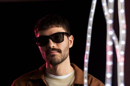 Photo for man in sunglasses over neon lights at nightclub - Royalty Free Image