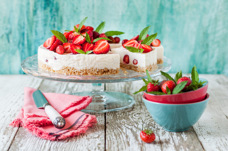 Photo for Sliced No Bake Strawberry Cheesecake Decorated with Fresh Berries and Mint - Royalty Free Image