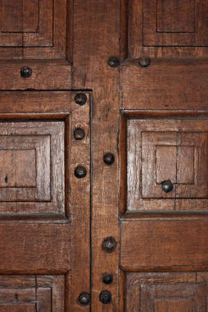 decorative designs of wooden doors in the old style framed by iron rivets and bolts