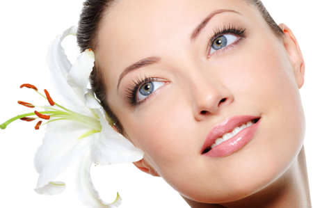 Healthy skin of young beautiful woman face with a flower in her hairs