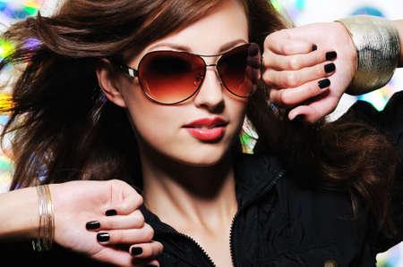 Glamour stylish beautiful  woman with fashion sunglasses and black manicure