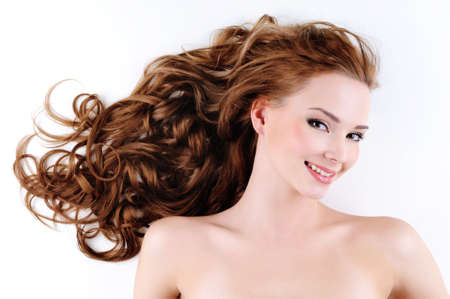Portrait of the happy beautiful  woman with brown long ringlets hair