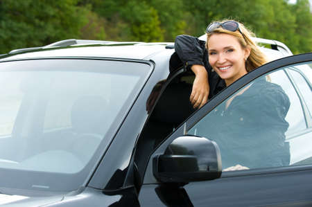 portrait of attractive young happy woman in the new car  - outdoors