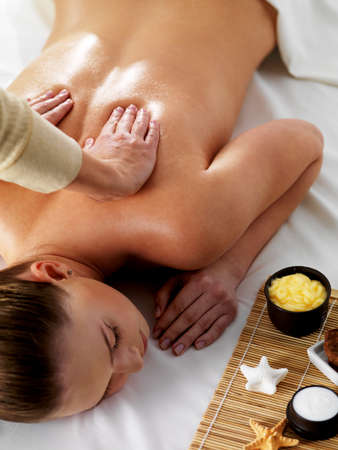 Relaxation and joy in massage for young beautiful woman in spa beauty salon - vertical