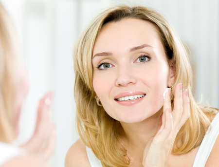 Beautiful young woman applying cosmetic cream on face standing in the bathroom