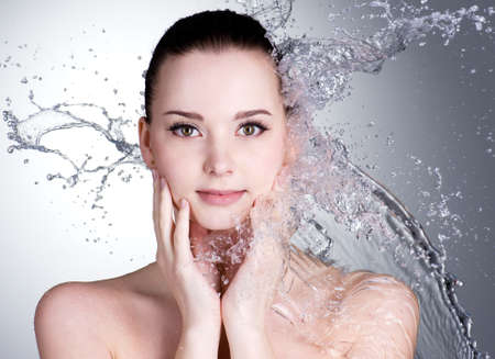 Splashes of water on the beautiful face of young woman - grey background
