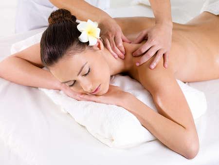 Woman in beauty salon having massage of shoulder   - horizontal