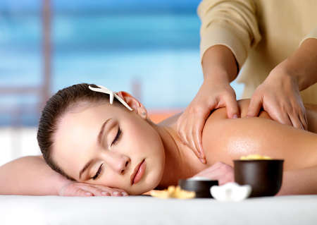Young beautiful relaxing woman getting spa massage of shoulder in beauty salon - nature background.