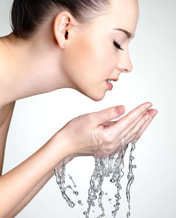 Profile portrait of beautiful woman washing  face with  water - studio
