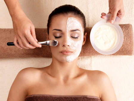 Photo for Spa therapy for young woman receiving facial mask at beauty salon - indoors - Royalty Free Image