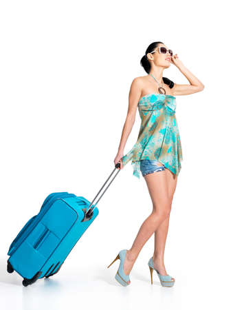 Foto de Full length of casual woman standing with travel suitcase - isolated on white background - Imagen libre de derechos