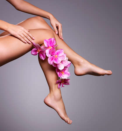 Beautiful long female legs with flower. Beauty treatment concept