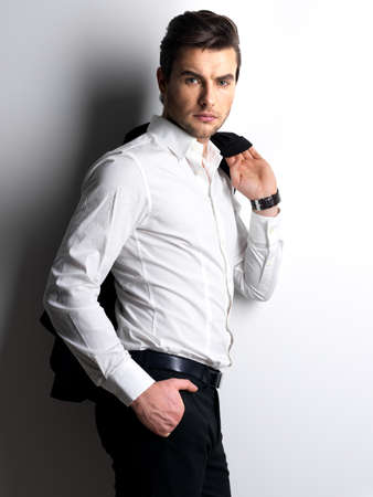 Foto de Fashion portrait of young man in white shirt poses over wall with contrast shadows - Imagen libre de derechos