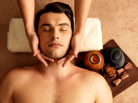 Masseur doing head massage on man in the spa salon.