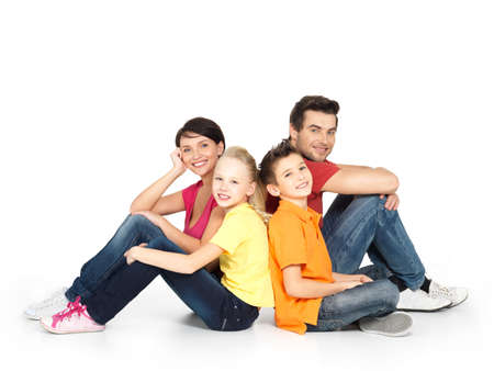 Foto de Portrait of the happy  family with two children sitting at studio on white floor - Imagen libre de derechos