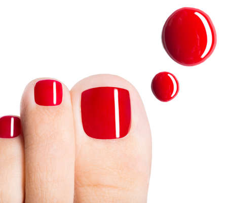 Foto de Beautiful female toes with red pedicure and drops of nail polish  over white background - Imagen libre de derechos