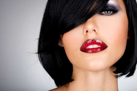 Photo for Beautiful brunette woman with shot hairstyle and sexy red lips. Closeup portrait of a female model with fashion makeup - Royalty Free Image