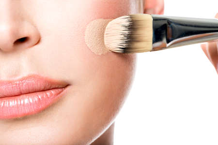 Photo pour Makeup artist applying liquid tonal foundation  on the face of the woman. Closeup photo of cheek - image libre de droit