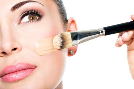 Photo pour Makeup artist applying liquid tonal foundation  on the face of the woman - image libre de droit