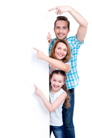 Foto de Portrait of an american family pointing by finger to the banner - isolated on a white background - Imagen libre de derechos