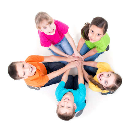 Foto de Group of happy children sitting on the floor in a circle holding hands and looking up - isolated on white. - Imagen libre de derechos