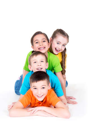Photo pour Five beautiful smiling kids lying on the floor in bright colorful t-shirts -  isolated on white. - image libre de droit