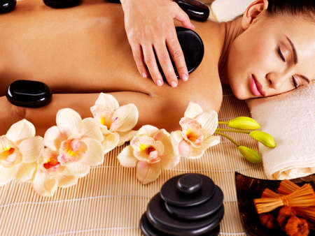 Photo for Adult woman having hot stone massage in spa salon. Beauty treatment concept. - Royalty Free Image