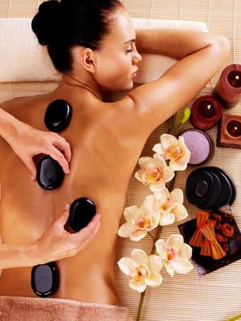 Photo pour Adult woman having hot stone massage in spa salon. Beauty treatment concept. - image libre de droit