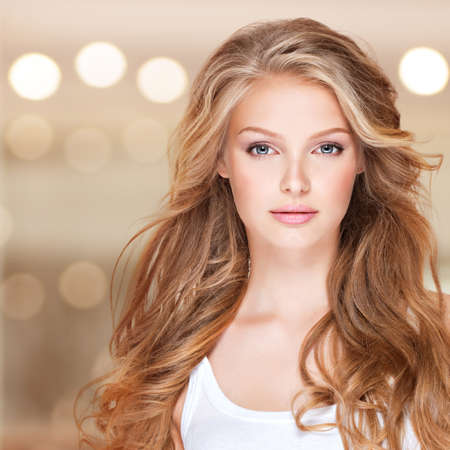 Photo for Portrait of beautiful young woman with long curly hair. Closeup face of a pretty caucasian model looking at camera - Royalty Free Image
